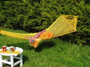 Hamac à barres Bora-Bora jaune créé par Filt dans un jardin